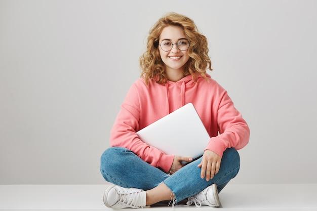 Studentessa intelligente allegra che si siede sul pavimento con il computer portatile