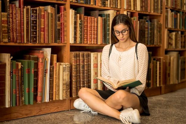 Studentessa messa a fuoco che si siede a gambe accavallate con il libro in biblioteca