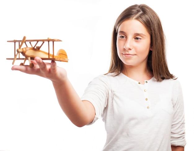 Studentessa mostrando un aeroplano di legno