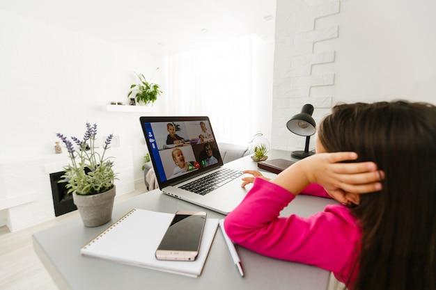 Studentessa piuttosto elegante che studia matematica a casa durante la sua lezione online a casa, distanza sociale durante la quarantena, autoisolamento, concetto di istruzione online, scuola a casa