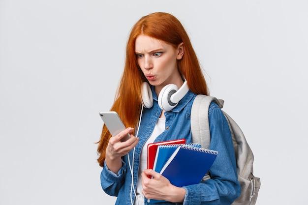 Studentessa rossa di bell'aspetto dispiaciuta, pazza o confusa, studente con zaino, quaderni e cuffie, lettura di strani messaggi sullo smartphone, accigliato,