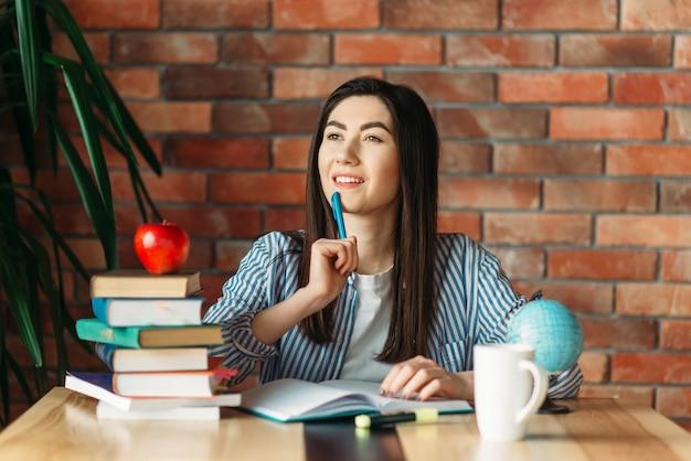 Studentessa seduta al tavolo con libri di testo