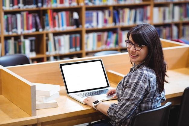 Studentessa sorridente che utilizza computer portatile nella biblioteca