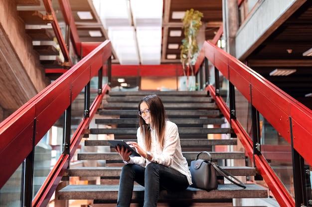 Studentessa sorridente con gli occhiali e capelli castani facendo uso della compressa mentre sedendosi sulle scale.