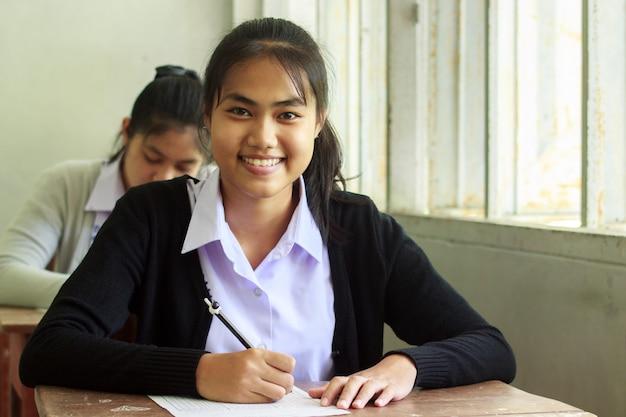 Studentessa sorridente e scrivendo esame senza stress.
