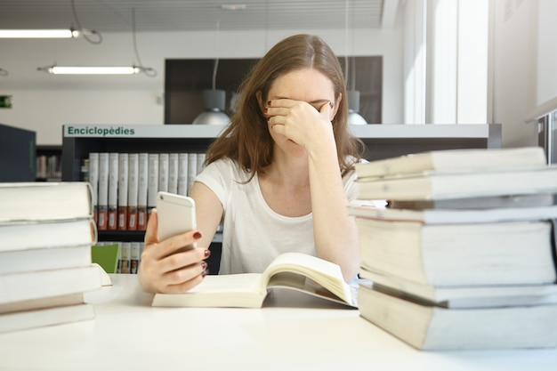 Studentessa stanca della scuola di economia seduta in biblioteca stropicciandosi gli occhi, annoiata di leggere il manuale di audit, controllando il tempo usando la sua applicazione per smartphone, circondata da pile di libri