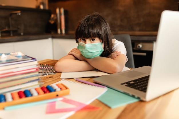 Studentessa studia a casa, distanza sociale durante la quarantena, autoisolamento, concetto di istruzione online, scuola a casa. apprendimento online durante la pandemia covid-19