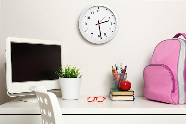 Studentessa sul posto di lavoro sulle pareti chiare dello sfondo