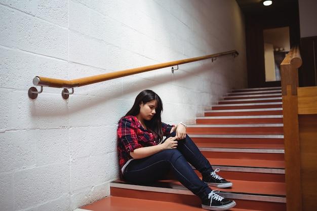 Studentessa turbata che si siede sulla scala