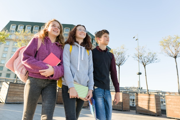 Studenti adolescenti sorridenti con zaini e libri di testo