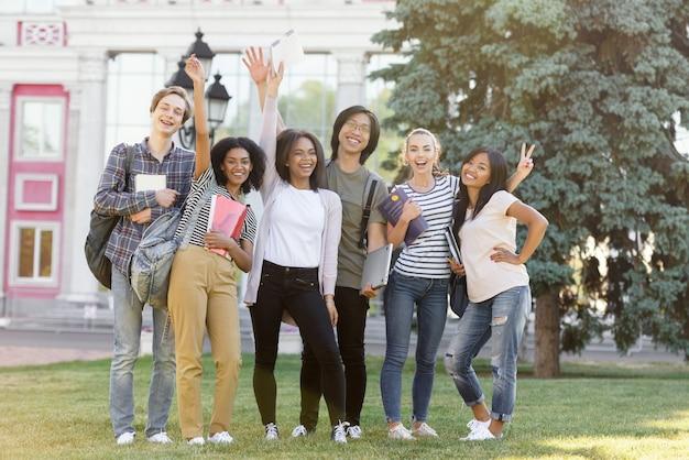 Studenti allegri che stanno e che ondeggiano all'aperto