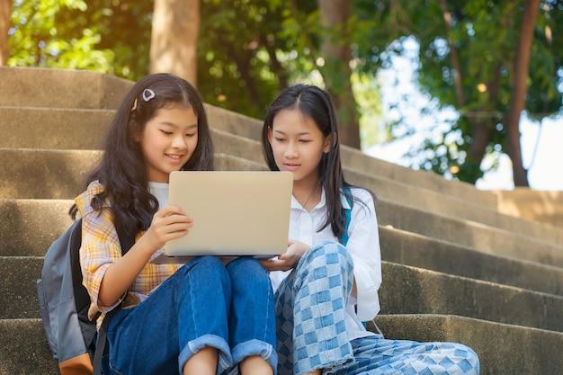 Studenti asiatici giovani insieme lettura libro di studio sorridente con tablet, computer portatile al campus della scuola superiore, college in vacanza estiva relax
