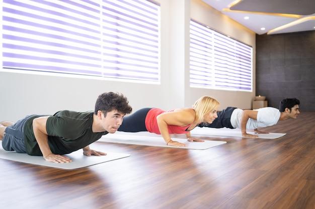 Studenti concentrati che praticano yoga a lezione