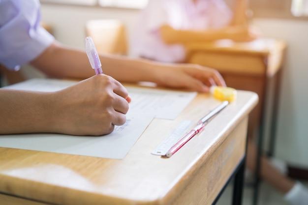 Studenti dell'istruzione uniforme che esaminano l'esame con la matita per i quiz a scelta multipla o l'esame di prova