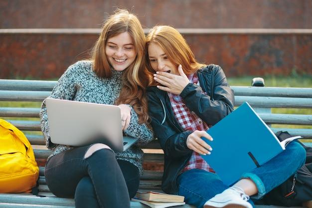 Studenti di college che guardano sorridere dello schermo del computer portatile sorpreso