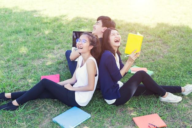 Studenti di felicità che leggono e che si siedono sulla terra a scuola.