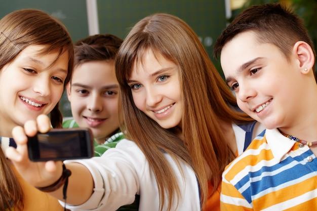 Studenti felice prendendo selfie in classe