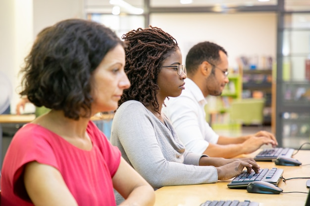 Studenti impegnati in un mix serio che lavoravano in classe informatica