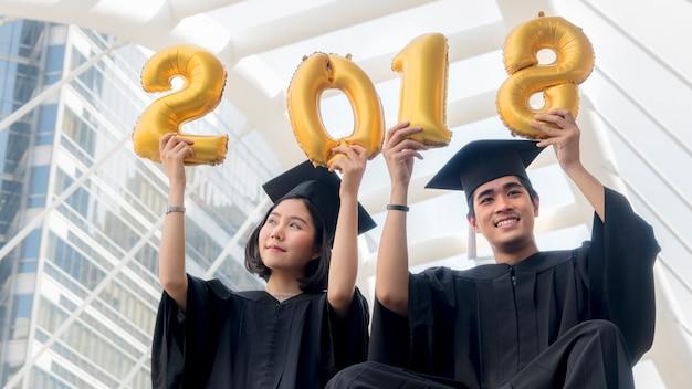 Studenti in abito di laurea sedersi e numeri d'oro palloncini 2018