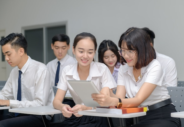 Studenti in uniforme che lavorano con il tablet