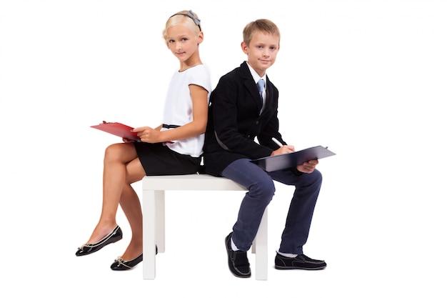 Studenti in vestiti di affari sulla discussione bianca del fondo