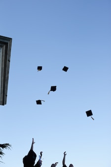 Studenti laureati che gettano il cappello in cielo