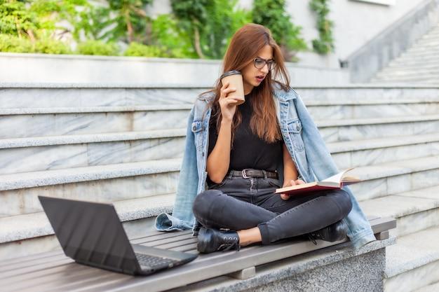 Studenti moderni. insegnamento a distanza. la giovane donna entusiasta legge il libro mentre si siede sul banco con un computer portatile