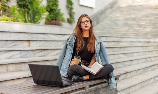 Studenti moderni. insegnamento a distanza. la ragazza giovane dei pantaloni a vita bassa legge il libro mentre si siede su un banco con un computer portatile