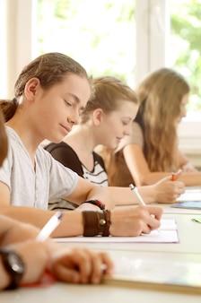 Studenti o alunni che scrivono test a scuola concentrati