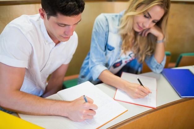 Studenti seri che scrivono durante le lezioni all'università