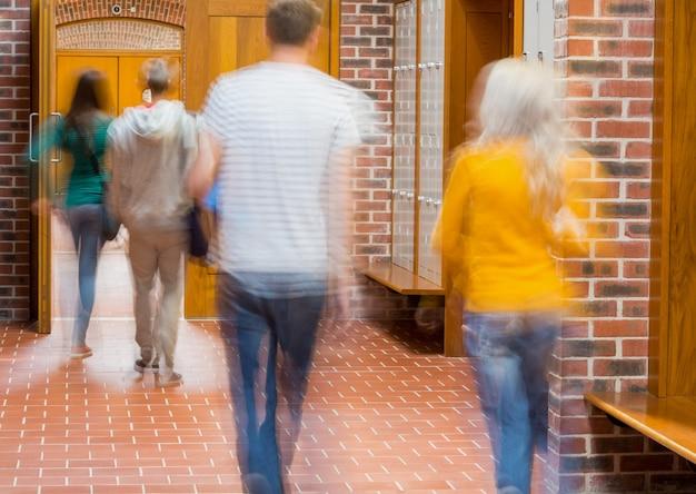 Studenti sfocati che camminano attraverso il corridoio