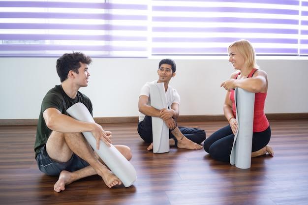 Studenti sorridenti che chiacchierano dopo la lezione di yoga