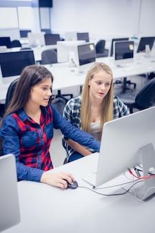 Studenti sorridenti che utilizzano computer all'università