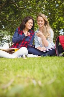 Studenti sorridenti che utilizzano smartphone al parco