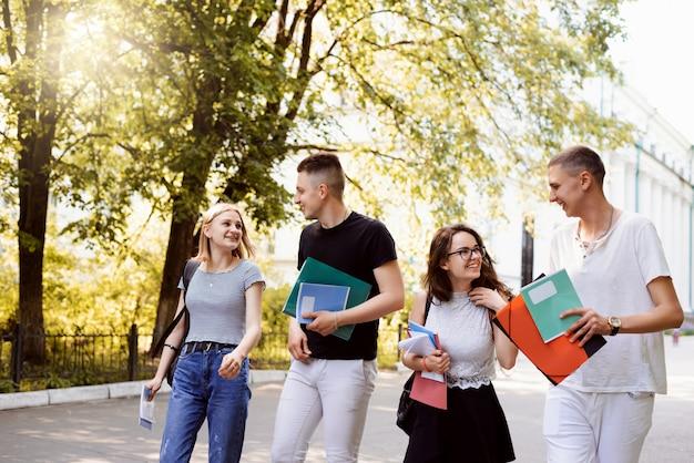 Studenti universitari che camminano verso la residenza dopo lezioni e seminari, condividendo idee e conversando sulle lezioni. gli studenti che camminano nel parco la sera