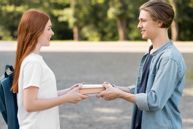 Studenti universitari che scambiano libro