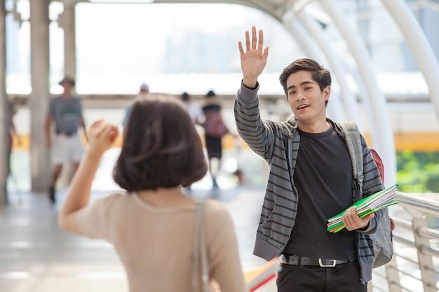 Studenti uomo e donna che tengono molti libri agitando le mani salutano i loro amici
