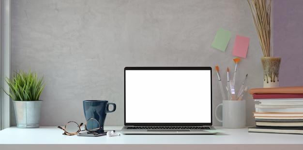 Studio creativo dell'artista con gli strumenti del computer portatile e della pittura dello schermo in bianco