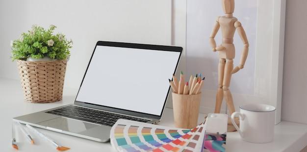 Studio creativo dell'artista moderno con il computer portatile dello schermo in bianco, i campioni di colore e gli articoli per ufficio