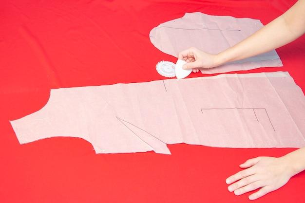 Studio di cucito. una sarta circonda un capo di abbigliamento su un tessuto. vestiti da cucire. panno rosso