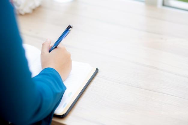 Studio di seduta della donna asiatica della mano del primo piano ed imparare a scrivere taccuino