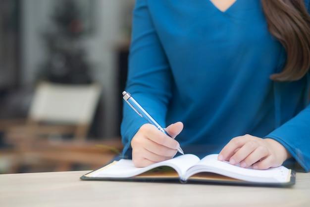 Studio di seduta della donna asiatica della mano del primo piano ed imparare taccuino e diario di scrittura sulla tavola