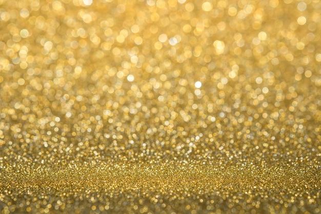 Studio scintillante dell'oro astratto della parete di scintillio e del fondo di prospettiva del pavimento con il bokeh della sfuocatura