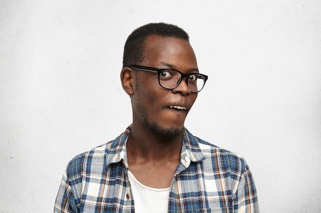 Studio shot di elegante maschio africano in bicchieri fissando la fotocamera, con uno sguardo pazzo