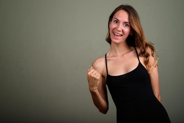 Studio shot di giovane bella donna che indossa top senza maniche su sfondo colorato