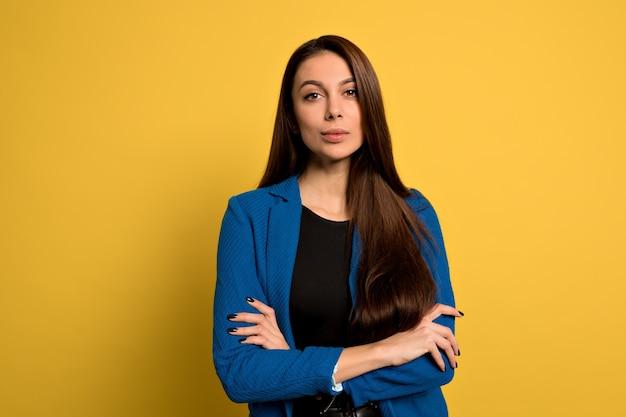 Studio shot di giovane donna sicura di sé con lunghi capelli scuri che indossa giacca blu in posa