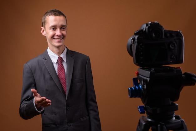 Studio shot di giovane imprenditore su marrone