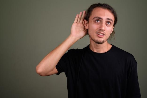 Studio shot di giovane uomo bello che indossa la camicia nera su sfondo colorato
