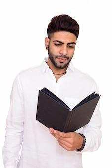 Studio shot di giovane uomo indiano bello lettura isolato su sfondo bianco
