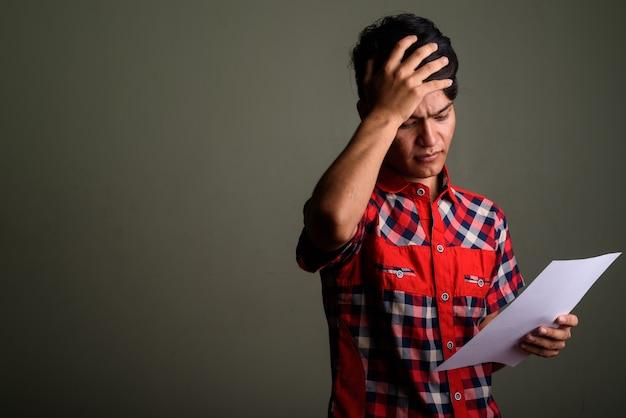 Studio shot di giovani adolescenti uomo che indossa la camicia a scacchi rossa contro colorato